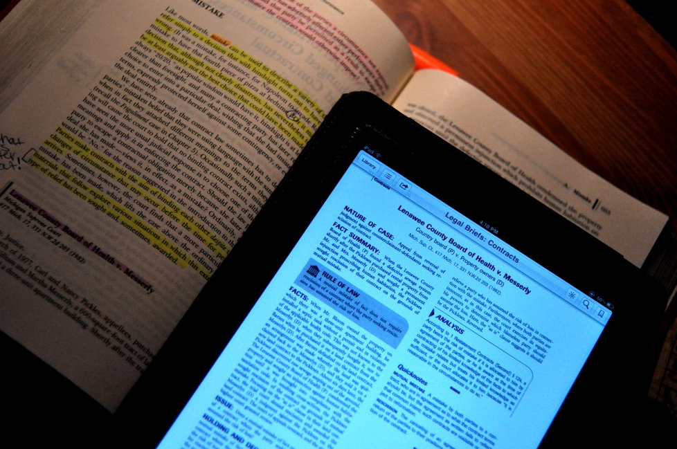 A tablet and a textbook set out as study materials