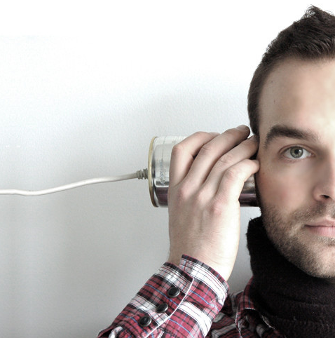 A man listens through a can connected to a wire