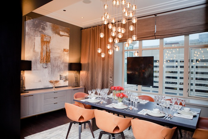 A swanky dining room with modern chandelier, fully set table