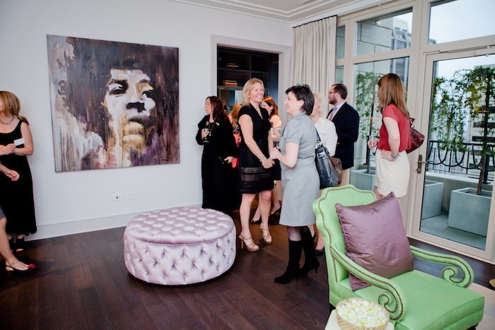 A group of people tour a home, where an abstract painting of Jimi Hendrix hangs on the wall