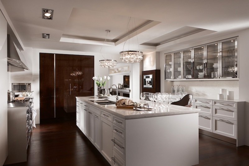 A swanky kitchen with chandeliers, kitchen island and glass cabinets