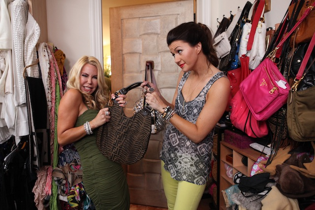 Two women hold a purse in a closet full of purses