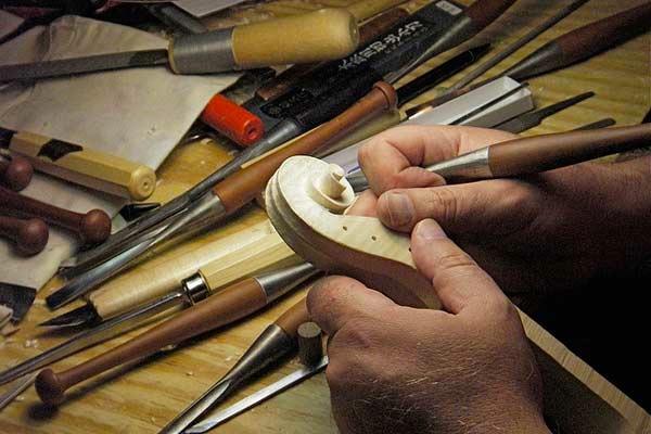 Hands handcrafting a violin handle