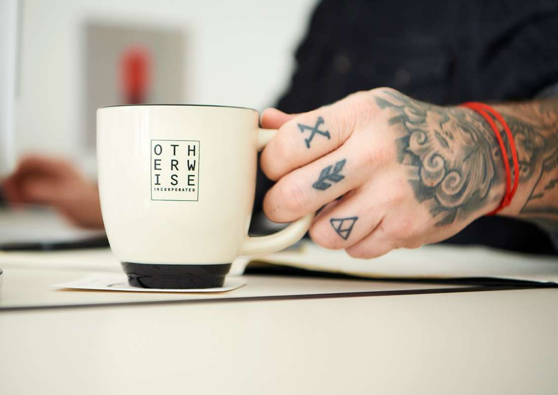 A tattooed hand holds a mug with the Otherwise logo