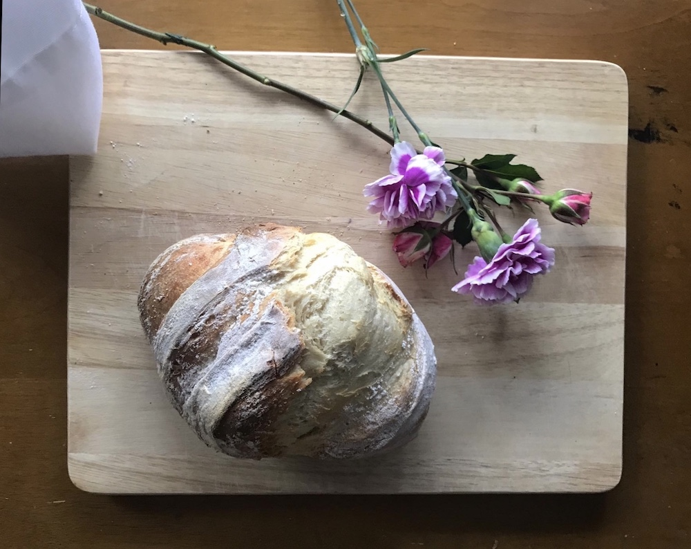 A loaf of bread next to flowers