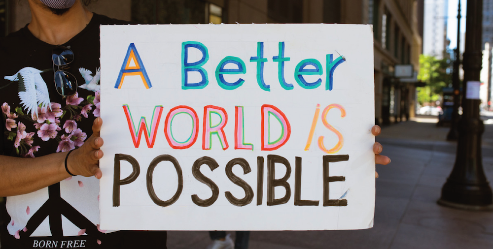 "Protester in Chicago holds up a sign that reads ""A better world is possible"""