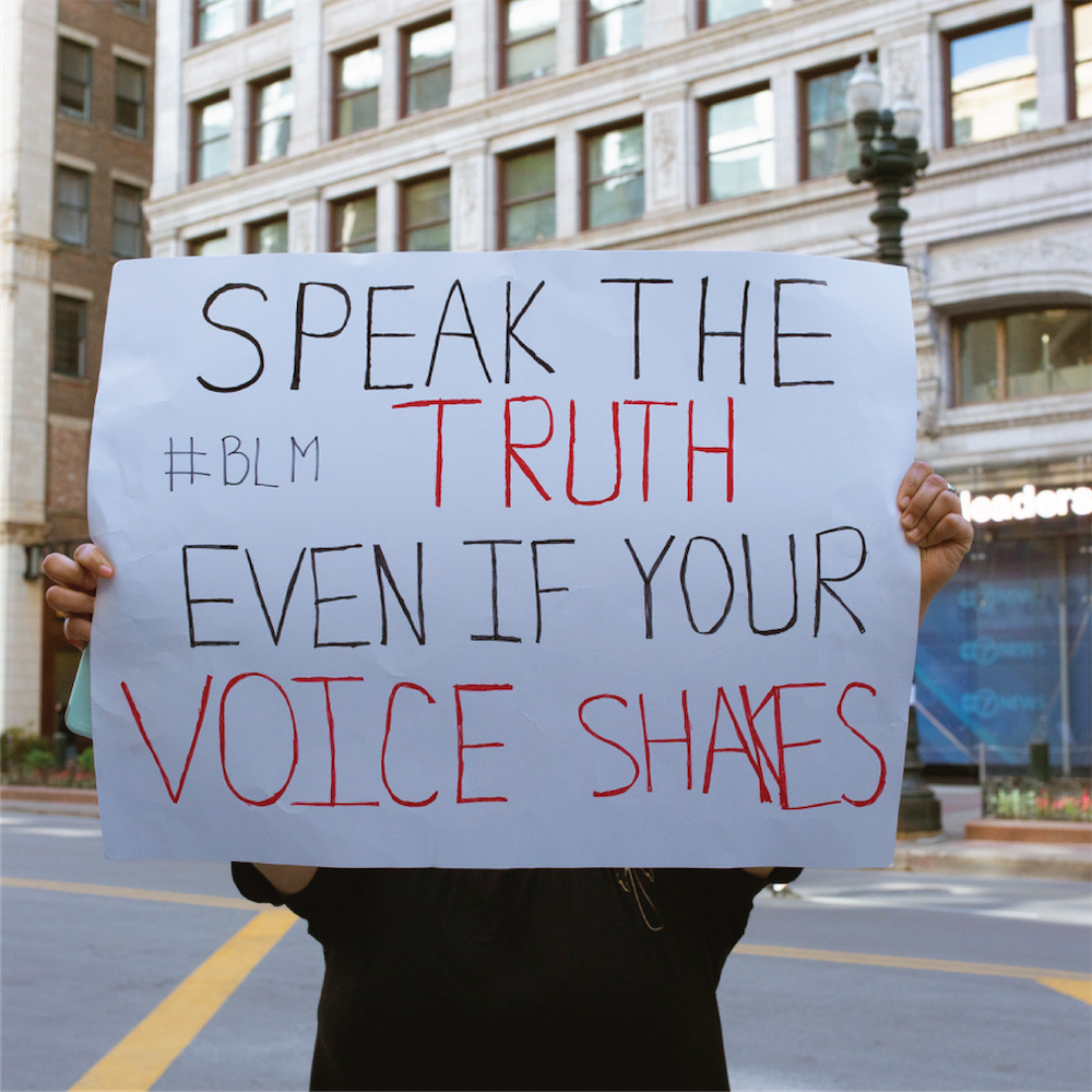 "Protester in Chicago holds up a sign that reads ""Speak the truth even if your voice shakes"""