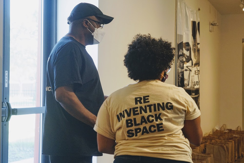 "Two volunteers pack bags of food at a community-led food bank. One volunteer's shirt reads ""Reinventing black space"" on the back"