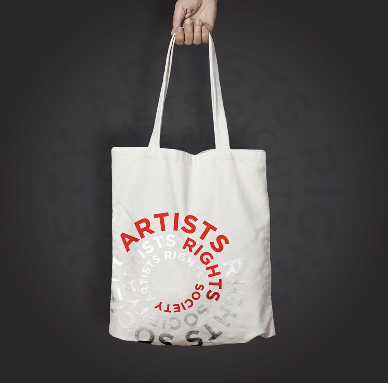 Hand holding a tote bag with the ARS logo