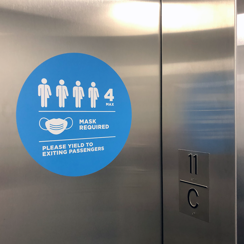 """Wayfinding sign on an elevator door that reads """"Mask required, please yield to exiting passengers"""" and has four people icons on it to show capacity"""