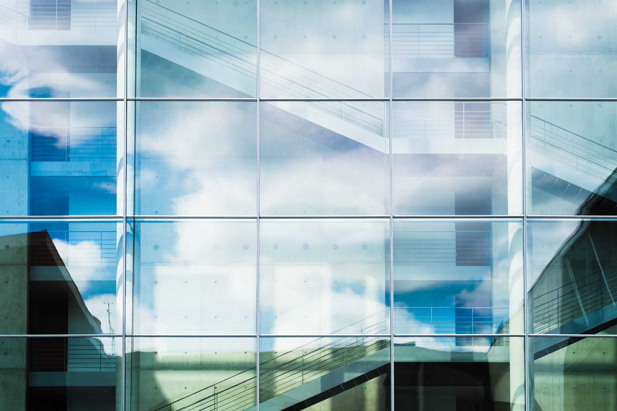 Photo of clouds and blue sky reflected in a clean glass window