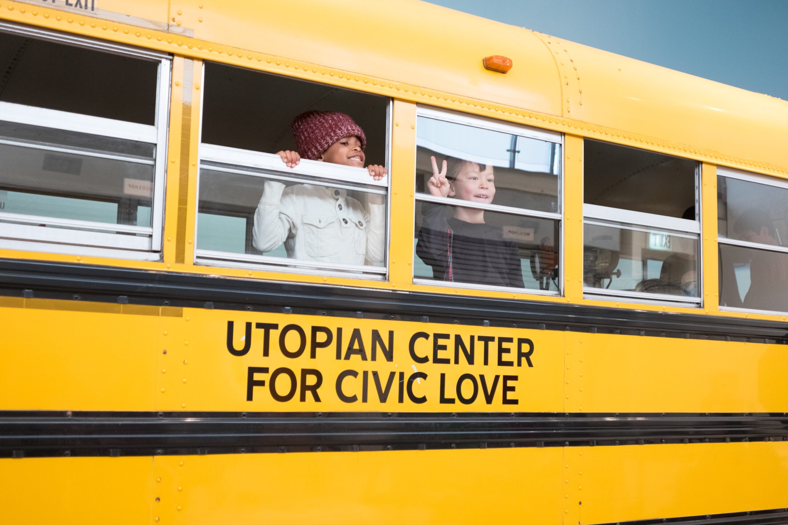"""Two children look out of a yellow school bus with the words """"Utopian Center for Civic Love"""" in black lettering"""