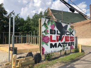 A plywood mural that says Black Lives Matter in the new Sounding Boards Garden at Harmony